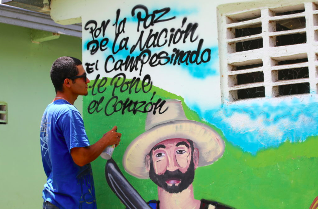 "Media credit: Jean-Pierre Larroque, courtesy of One Earth Future Foundation The mural reads, ""For national peace, the farmer puts down his heart."""
